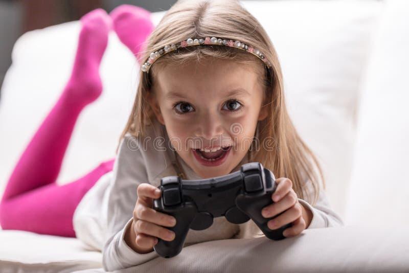 Petite fille jouant des jeux vidéo à la maison photographie stock libre de droits