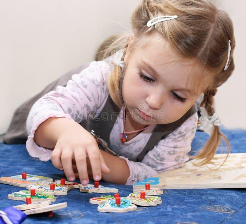 Petite fille jouant des puzzles en bois photos stock