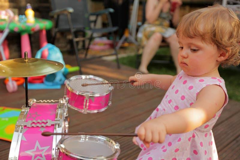 Petite fille jouant des tambours photos stock