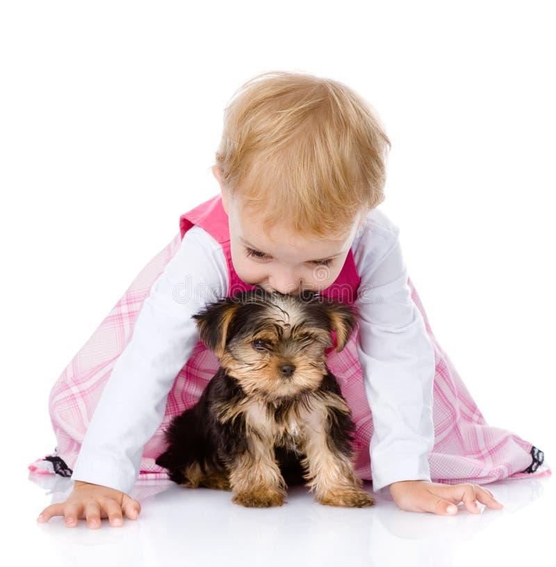 Petite fille jouant et rampant avec un chiot D'isolement sur le blanc photo libre de droits