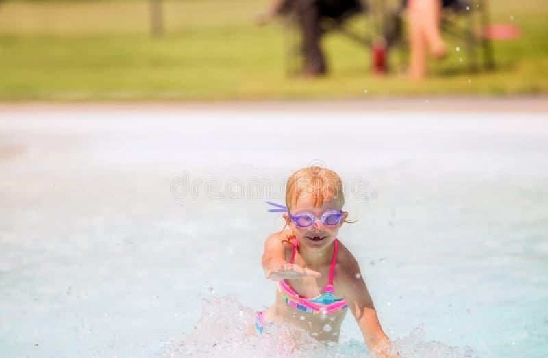 Petite fille jouant et riant dans une piscine images stock