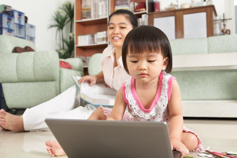 Petite fille jouant l'ordinateur portatif photographie stock