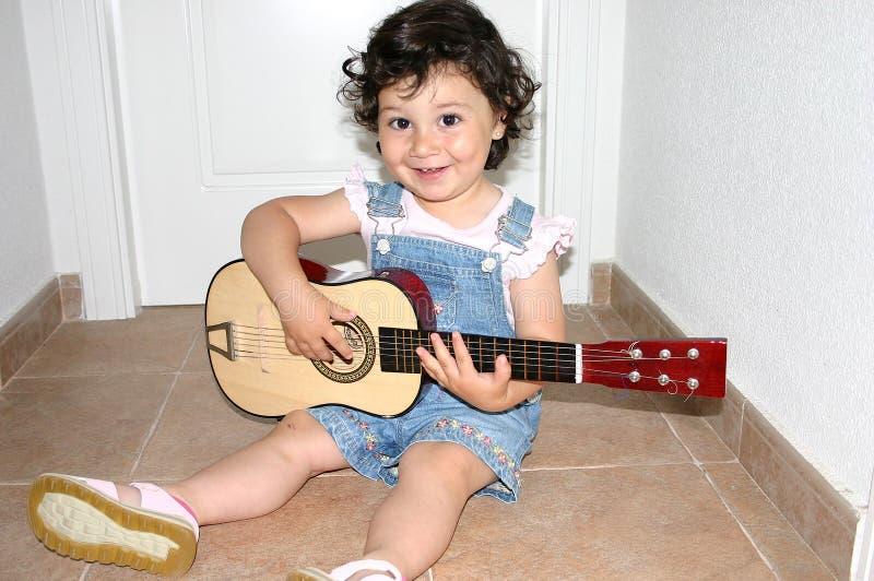 Petite fille jouant la guitare photo stock