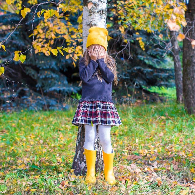 Petite fille jouant le cache-cache dans la forêt d'automne photographie stock