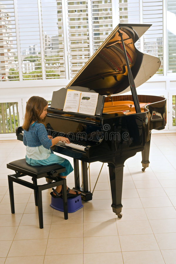 Petite fille jouant le piano images stock