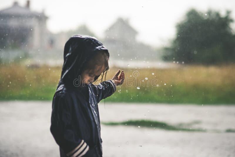 Petite fille jouant le seul extérieur en mauvais temps image libre de droits