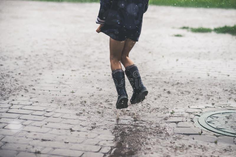 Petite fille jouant le seul extérieur en mauvais temps photo libre de droits