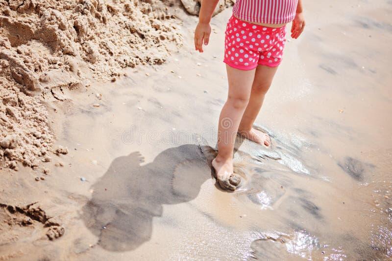 Petite fille jouant sur la plage photo stock