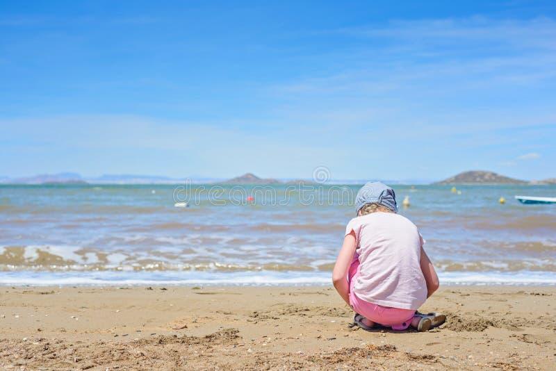 Petite fille jouant sur la plage de mars Menor photographie stock