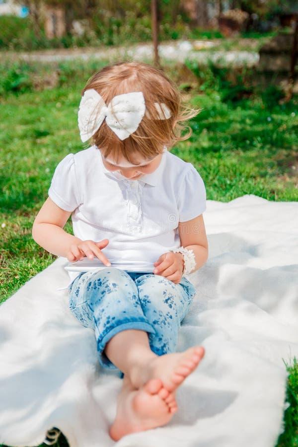 Petite fille jouant sur le comprimé Fille à l'aide d'un comprimé images libres de droits