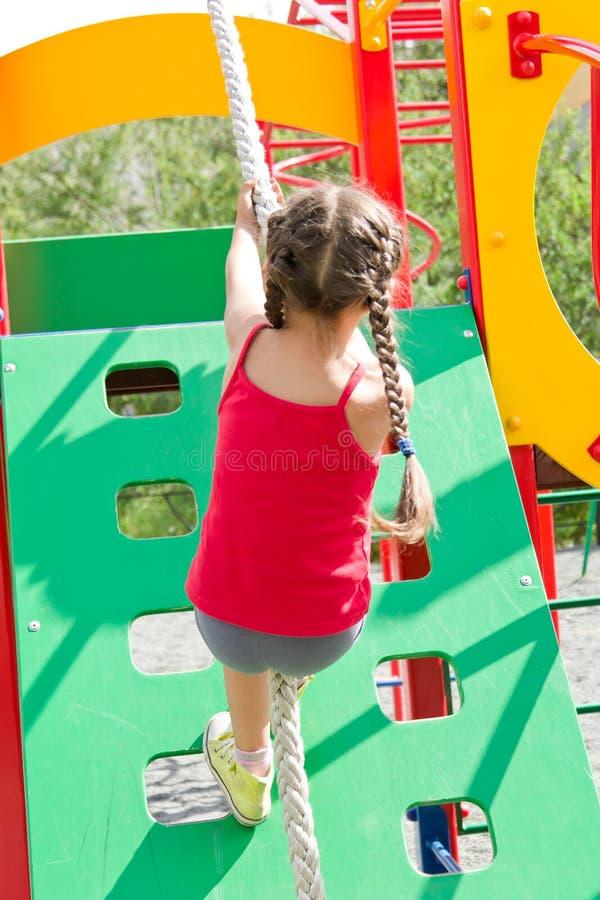Petite fille jouant sur le terrain de jeu, escaladant le mur sur la corde images stock