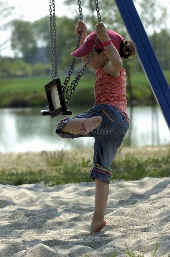 petite fille jouant sur une oscillation photographie stock libre de droits
