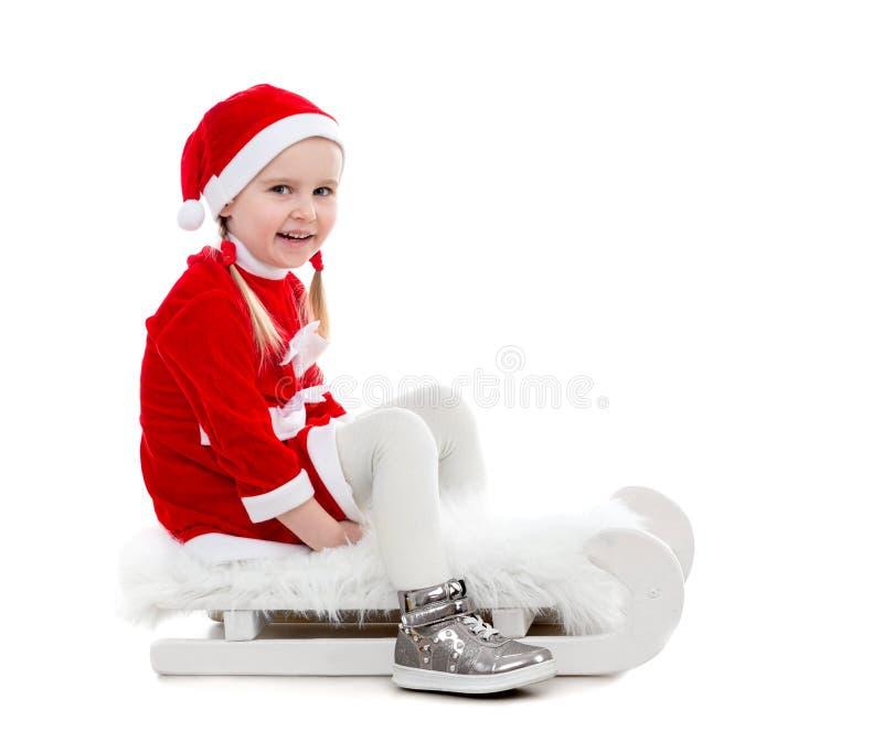 Petite fille joyeuse dans le costume de Santa se reposant sur un traîneau images libres de droits