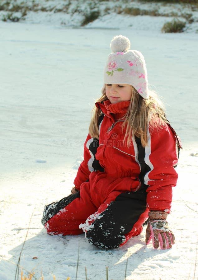 Petite fille kneeing sur l'étang glacé image libre de droits
