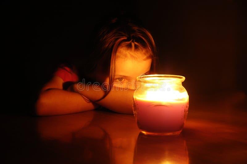 Petite fille la nuit regardant fixement la bougie rougeoyante de Lit photographie stock libre de droits