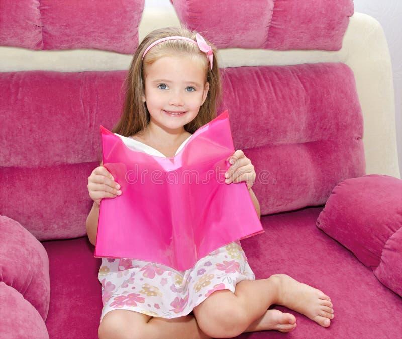 Petite fille lisant un livre et le situant sur le sofa photo libre de droits