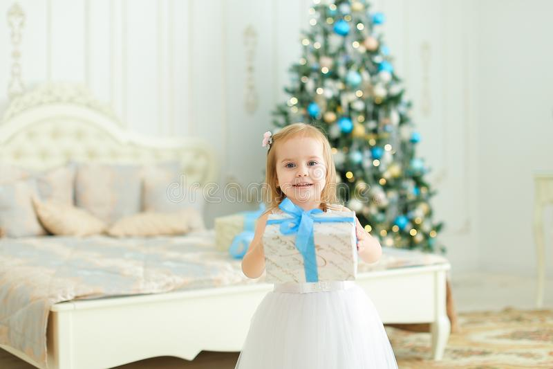 Petite fille maintenant le présent, la robe blanche de port et la position dans la chambre à coucher avec l'arbre de Noël image stock