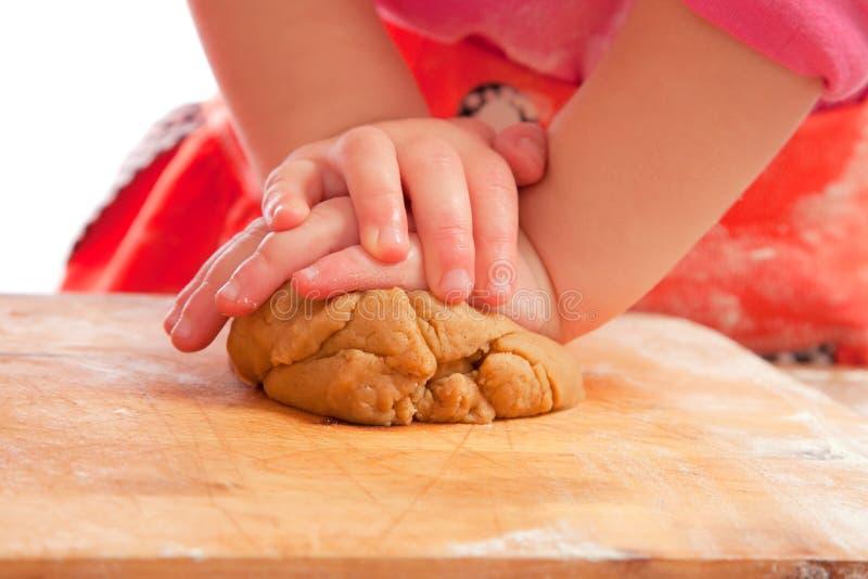 Petite fille malaxant une pâte de pain d'épice photos libres de droits