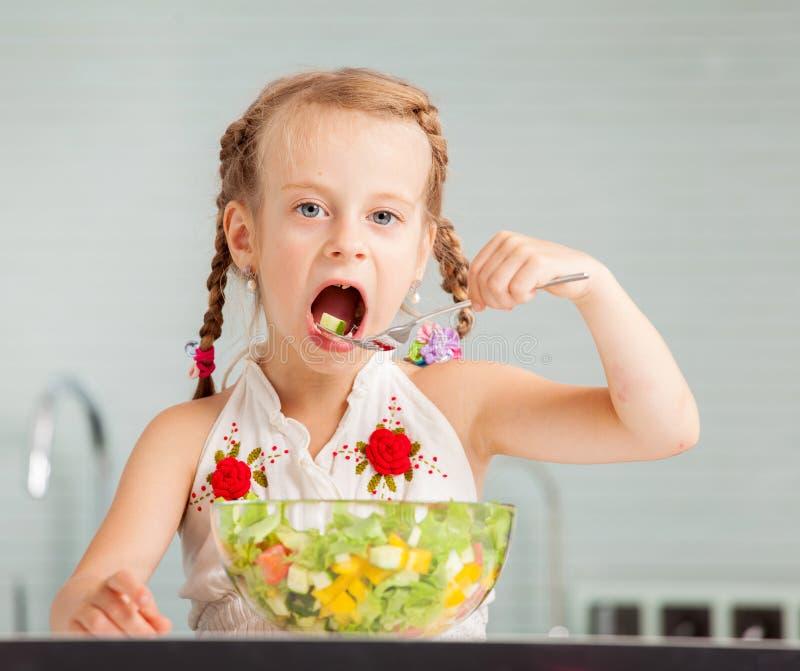 Petite fille mangeant de la salade végétale photos stock