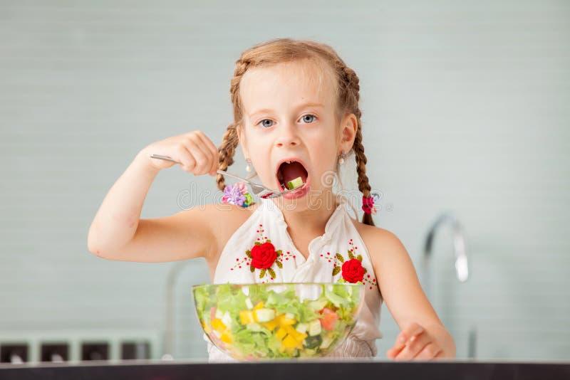 Petite fille mangeant de la salade végétale image libre de droits