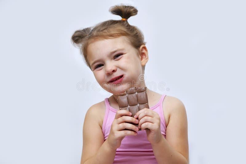 Petite fille mangeant du chocolat isolé sur blanc images libres de droits