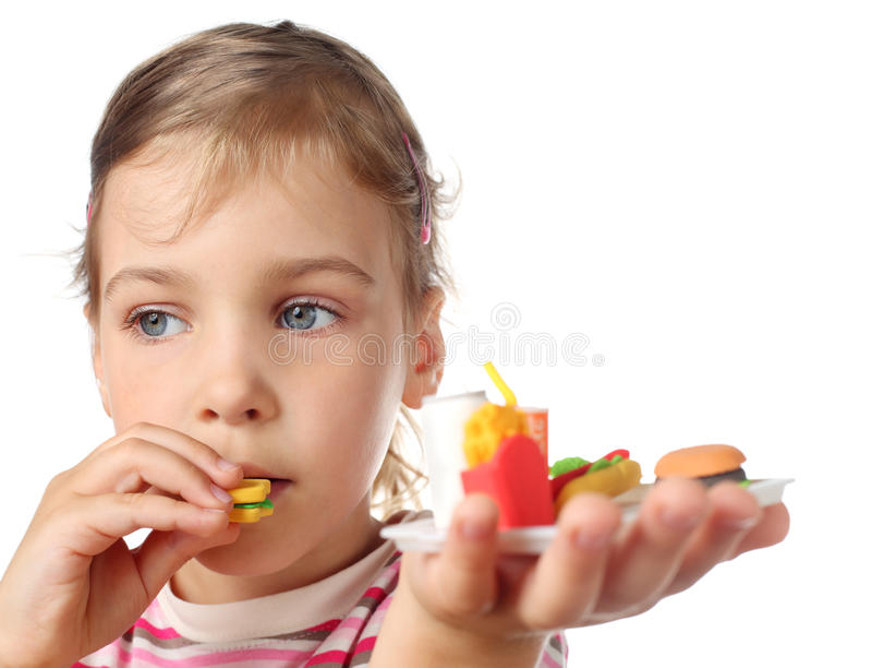 Petite fille mangeant l'hamburger de miniature de jouet images libres de droits