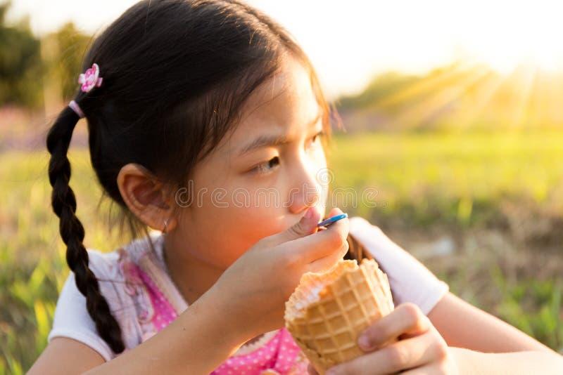 Petite fille mangeant la crème glacée dans le jardin à la lumière du soleil photos libres de droits
