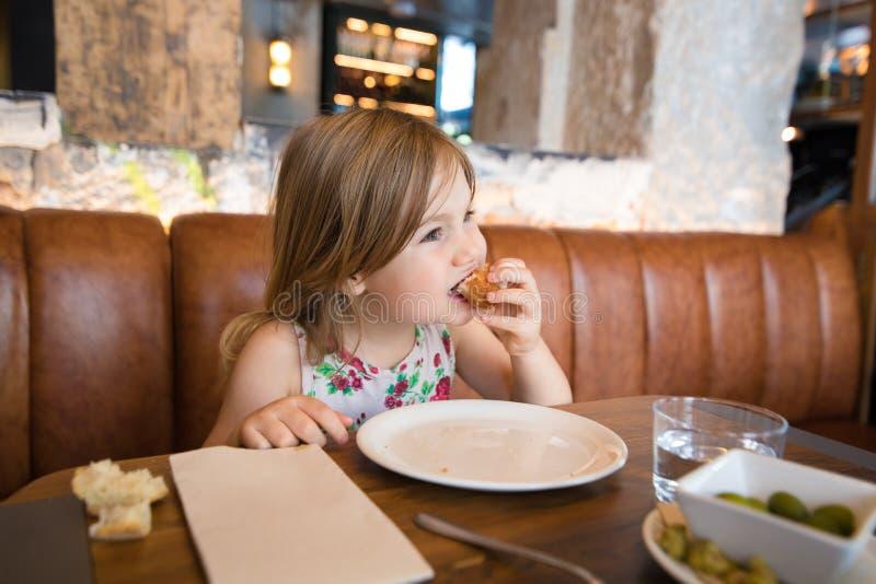 Petite fille mangeant la croquette avec la main dans le restaurant photos stock