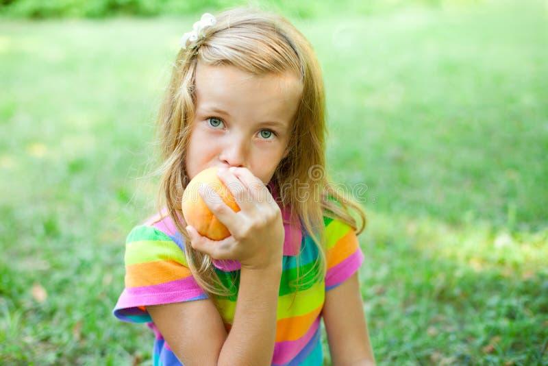 Petite fille mangeant la pêche photos libres de droits