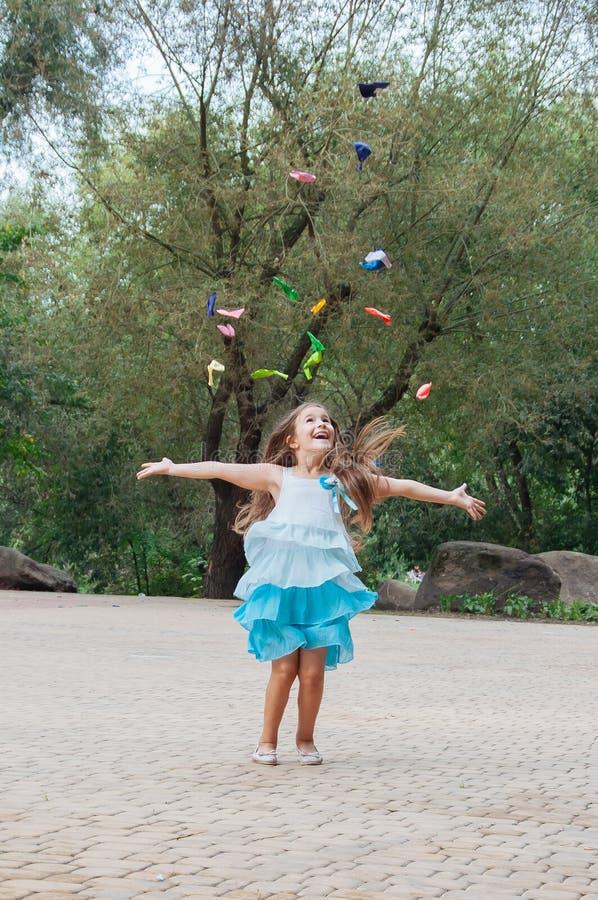 Petite fille mangeant la sucrerie de coton se reposant sur un banc pendant l'été de parc images stock