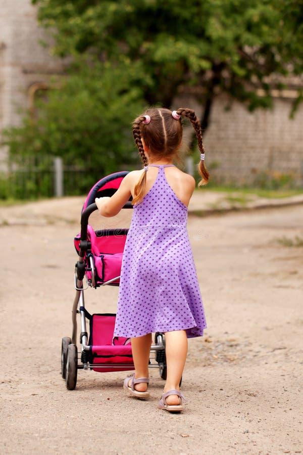 Petite fille marchant avec la poussette de jouet. Petite maman. photographie stock libre de droits