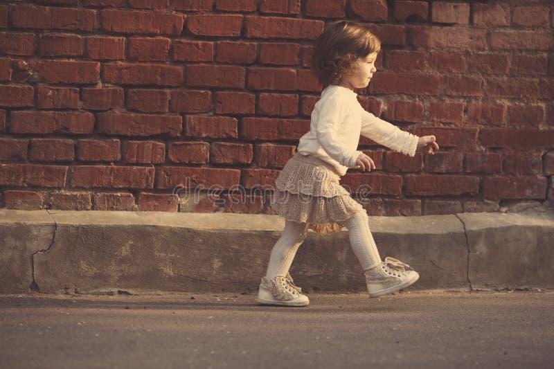 Download Petite fille marchant loin photo stock. Image du marche - 45350154