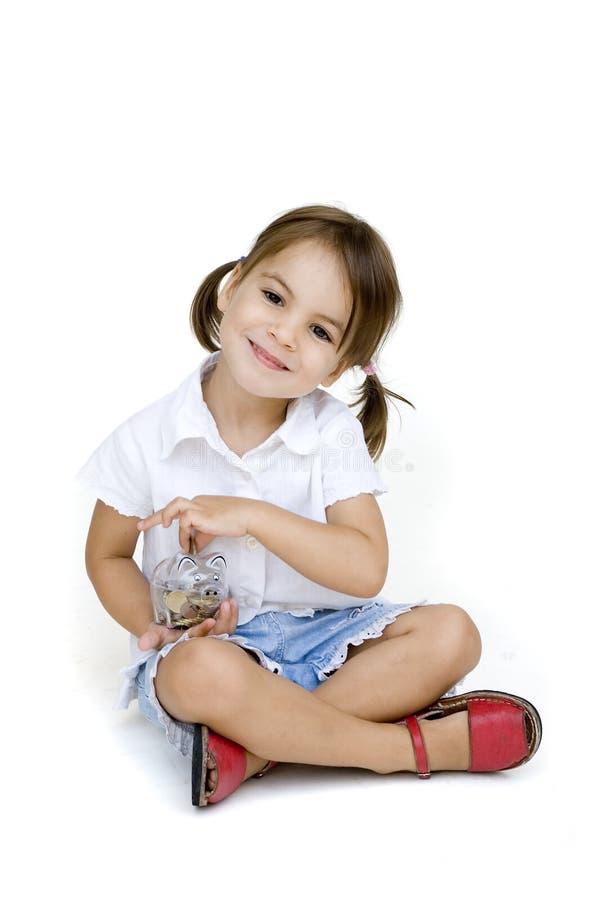 Petite fille mettant l'argent dans la tirelire photos stock