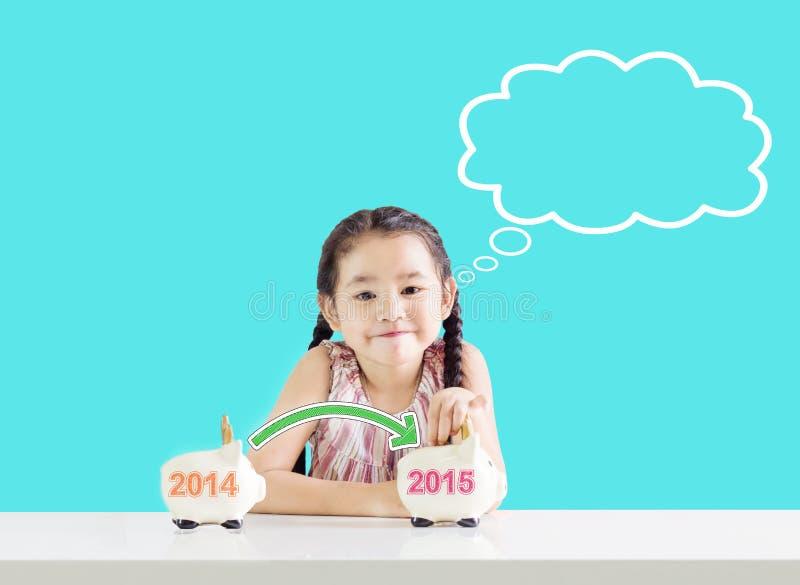 Petite fille mettant l'argent sur une tirelire avec une nouvelle année 2015 Penser à l'économie images stock