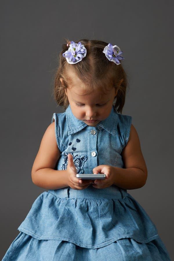 Petite fille mignonne à l'aide du smartphone Fond gris photos stock