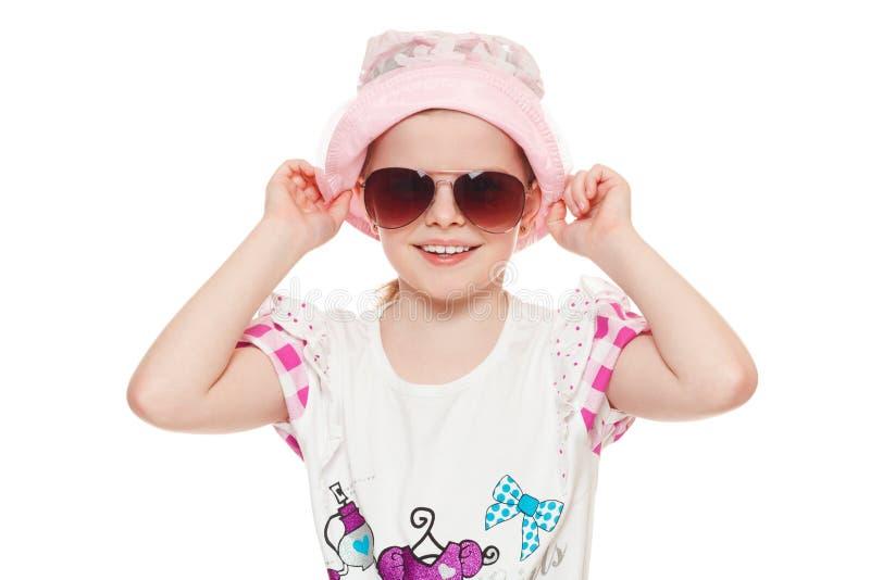 Petite fille mignonne à la mode dans les lunettes de soleil et le chapeau, d'isolement sur le fond blanc photographie stock