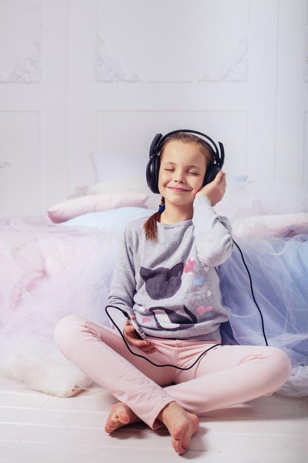 Petite fille mignonne écoutant la musique sur des écouteurs Le concept o photographie stock