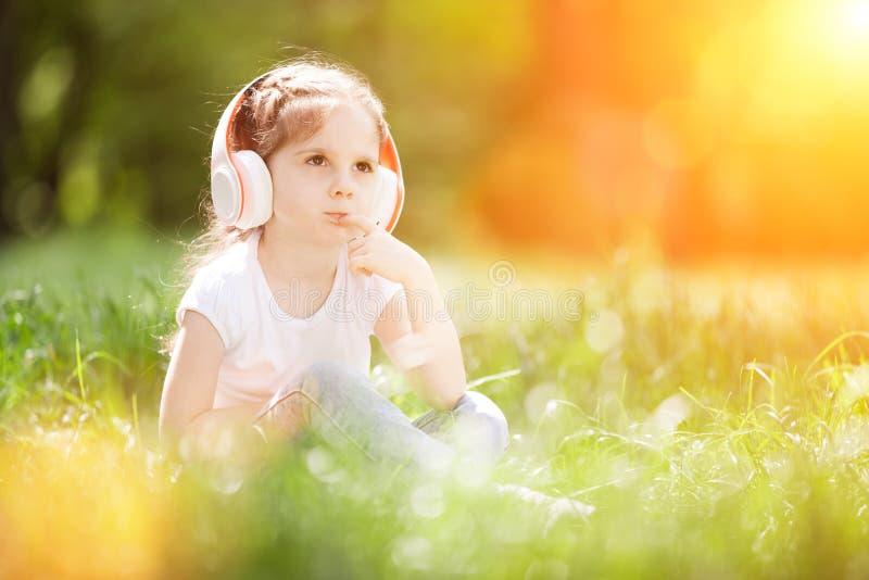 Petite fille mignonne écoute de la musique dans le parc d'automne Vie en plein air familiale Joyeux petit gosse dans les écouteur images stock