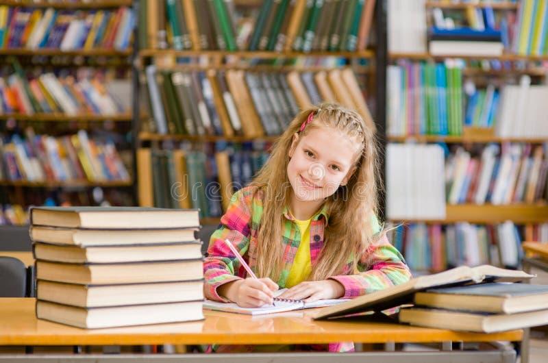 Petite fille mignonne étudiant à la bibliothèque et au sourire photo libre de droits