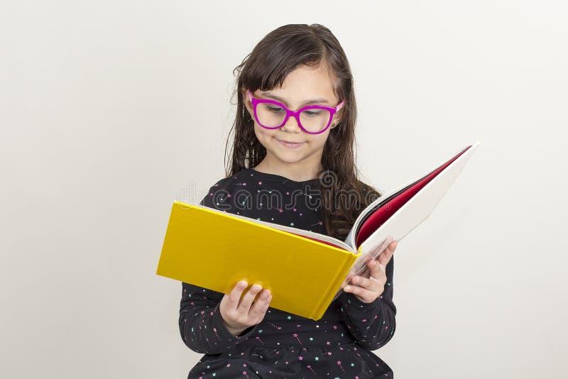 Petite fille mignonne affichant un livre photos stock