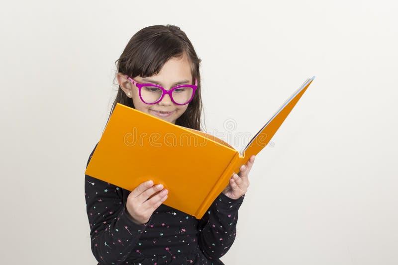 Petite fille mignonne affichant un livre photos libres de droits