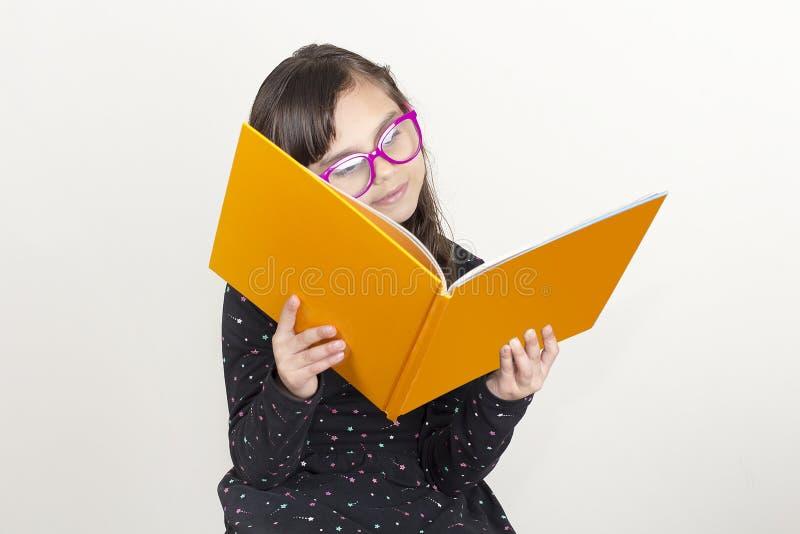 Petite fille mignonne affichant un livre images stock