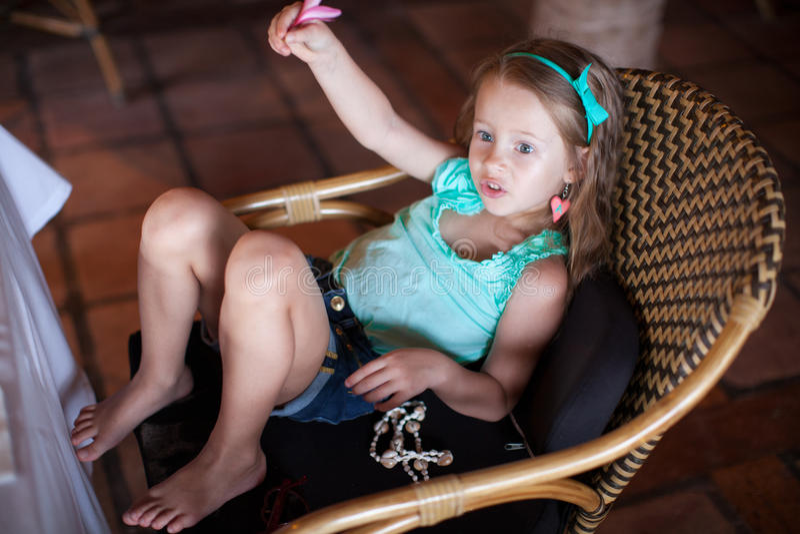 Petite fille mignonne appelle le serveur dans un restaurant photo libre de droits