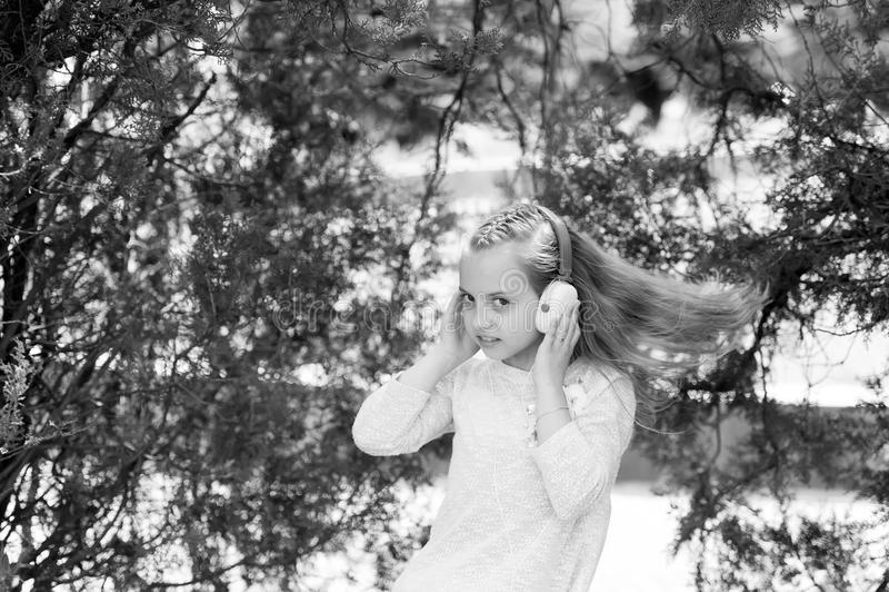 Petite fille mignonne appréciant la musique utilisant des écouteurs images stock