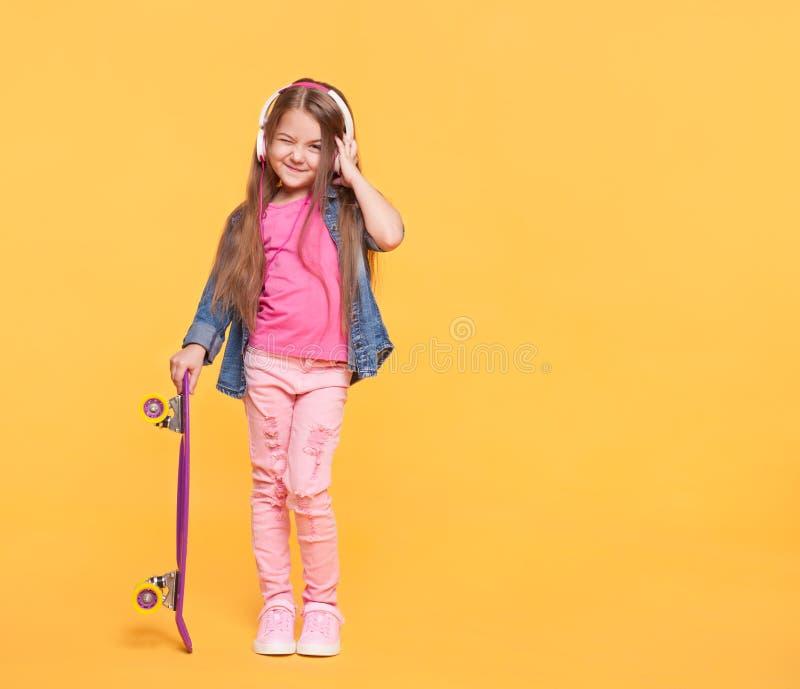 Petite fille mignonne appréciant la musique utilisant des écouteurs photographie stock libre de droits