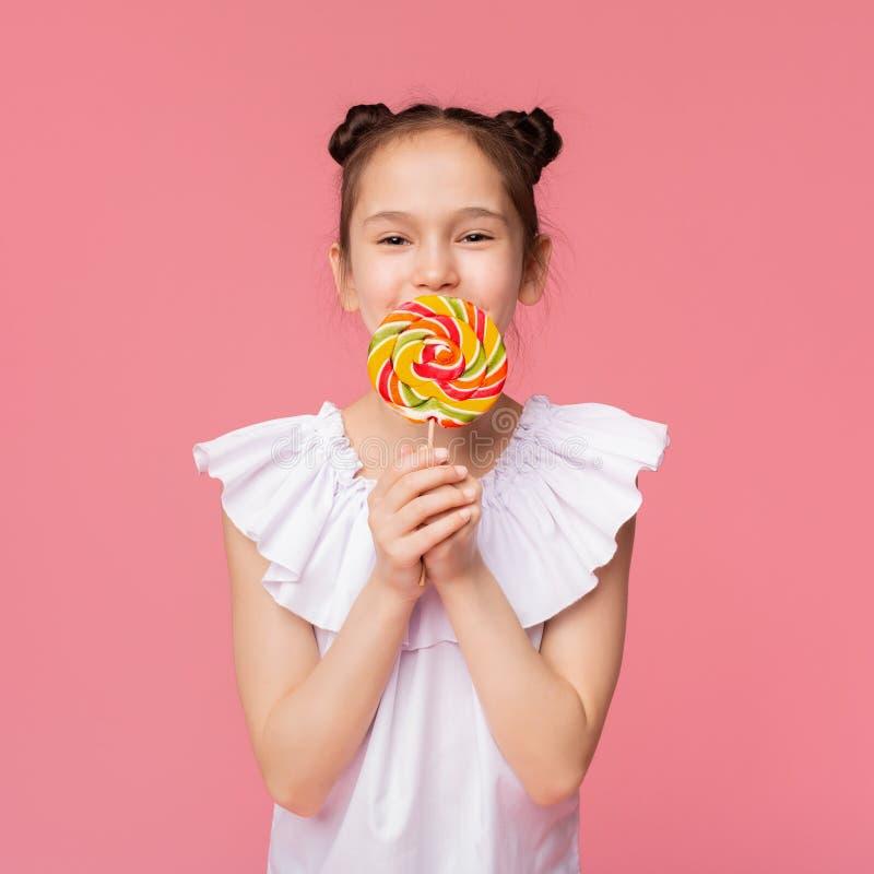 Petite fille mignonne appréciant la sucrerie, couvrant la bouche de grande lucette colorée image stock
