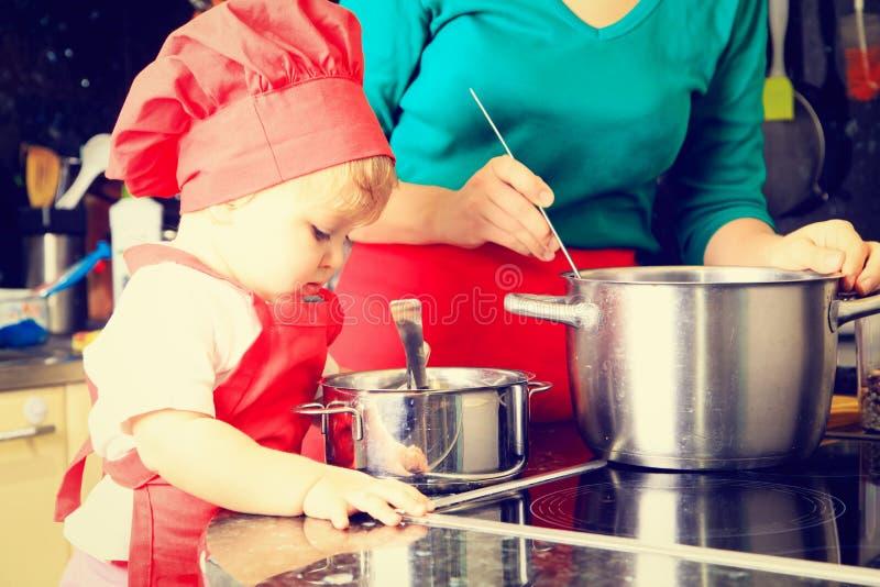 Petite fille mignonne apprenant à faire cuire avec la mère images libres de droits