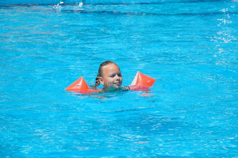 Petite fille mignonne apprenant comment nager dans la piscine dehors image stock