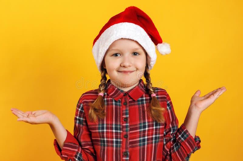 Petite fille mignonne au chapeau de santa arrosée Gros plan d'un enfant qui attend Noël sur fond jaune photo libre de droits