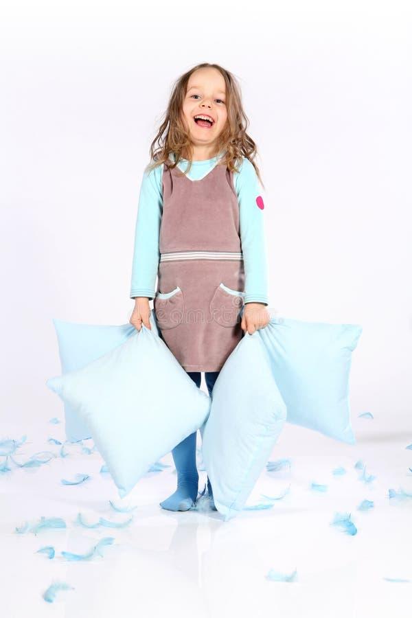 Petite fille mignonne avec des oreillers photographie stock